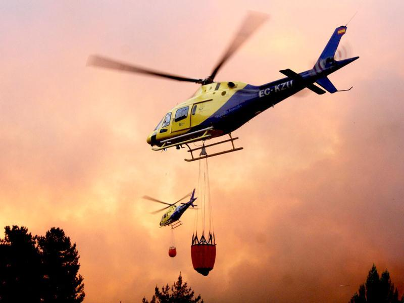 Helicopters fight a massive forest fire affecting the commune of Quillon, in southern Chile's Bio Bio region, some 500 Km south of Santiago