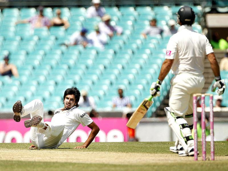 India's Ishant Sharma (L) rolls on the ground after attempting to field a shot from Australia's Ricky Ponting during the second cricket test match at the Sydney Cricket Ground. (Reuters)