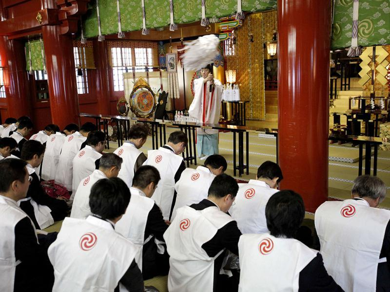 Groups of businessmen are purified by a Shinto priest during a ceremony on the first business day of New Year as they offer prayers, wishing for the prosperous business year, at Kanda Myojin in Tokyo. (AP Photo/Itsuo Inouye)