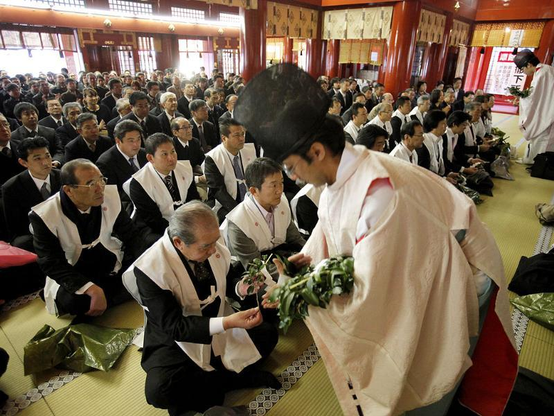 A Shinto priest hands sprigs of the sacred tree to businessmen during a ceremony on the first business day of New Year as they offer prayers, wishing for the prosperous business year, at Kanda Myojin in Tokyo. (AP Photo/Itsuo Inouye)