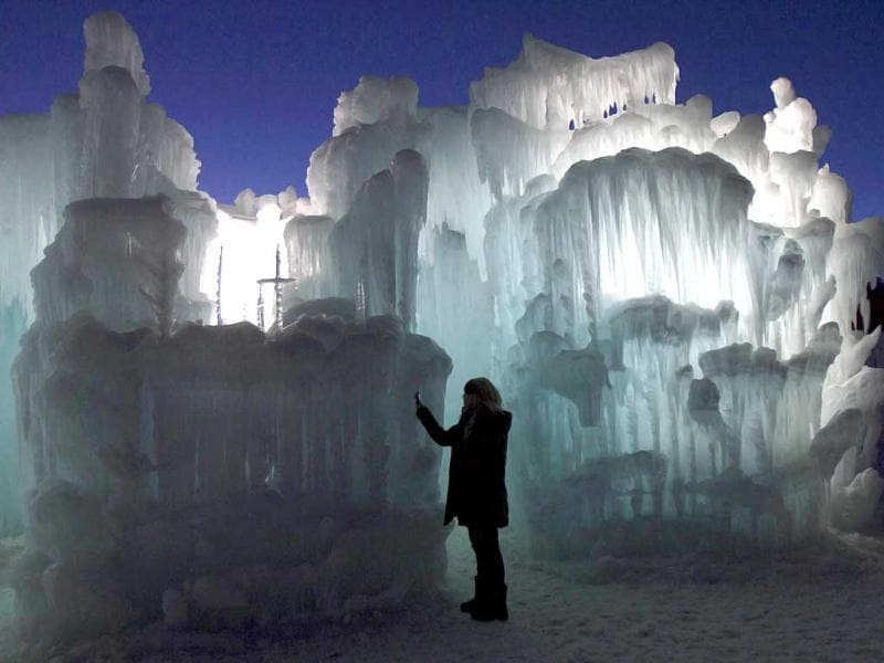 A tourist takes a photograph of ice formations at the ice castles in Silverthorne, Colorado. The ice castles consist of man-made walkways, tunnels, and arches of ice with no supporting structures, some reaching up to a height of 30 to 40 feet. Reuters/Nathan W Armes