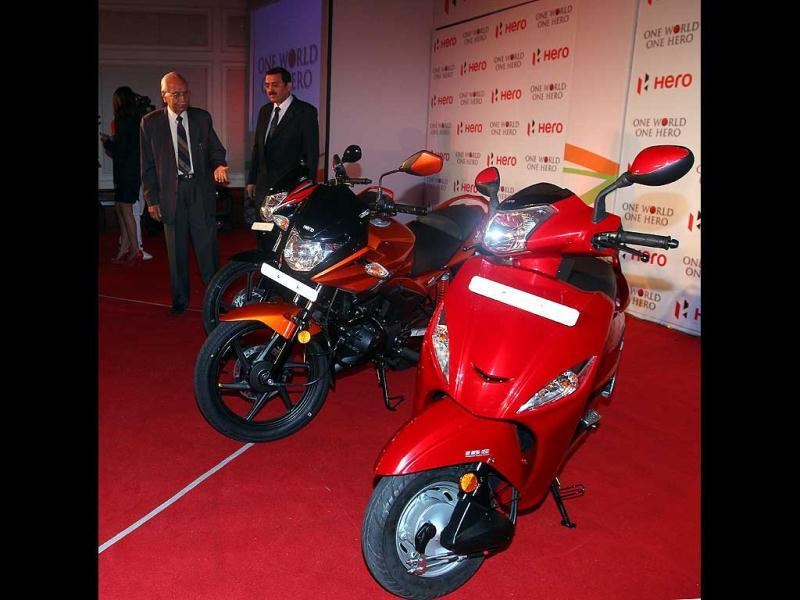 Founder and chairman Hero Motocrop Brij Mohan Lall Munjal (R) and joint managing director Hero Motocrop Sunil Kant Munjal pose with newly launched bikes 110cc passion Xpro, 125 cc Ignitor and scooter MAESTRO day before Auto Expo begins in New Delhi. HT Photo/Jasjeet Plaha