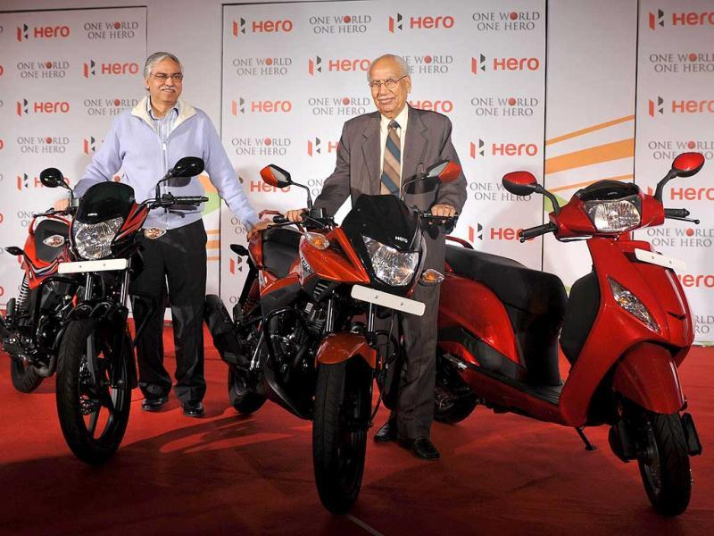 Founder and chairman Hero Motocrop Brij Mohan Lall Munjal (R) and joint managing director Hero Motocrop Sunil Kant Munjal pose with newly launched 110cc passion Xpro and 125 cc bike Ignitor day before Auto Expo begins in New Delhi. AFP Photo/Sajjad Hussain