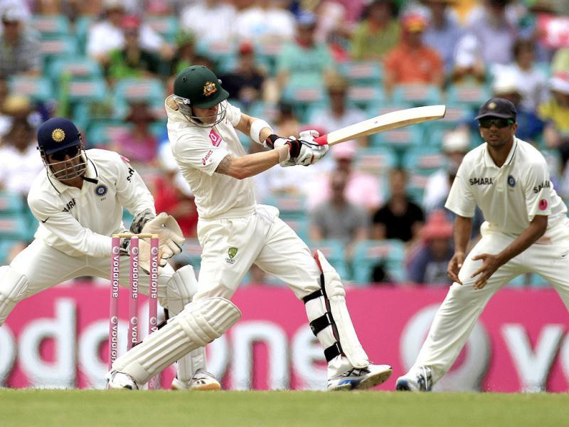 MS Dhoni, left, and Rahul Dravid, right, prepare to field as Australia's Michael Clarke pulls the ball on the third day in their cricket test match at the Sydney Cricket Ground in Sydney.(AP Photo)