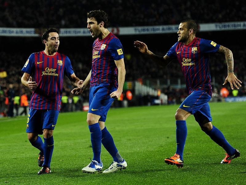 FC Barcelona's Cesc Fabregas, center, reacts after scoring his second goal with his teammate Xavi Hernandez, left, and Daniel Alves, from Brazil, right, against Osasuna during the first leg of a round of 16 Copa del Rey soccer match at the Camp Nou stadium, in Barcelona, Spain. (AP Photo/Manu Fernandez)