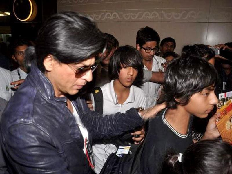 Shah Rukh holds Aryan as they move with the crowd at the Mumbai airport on Jan 3.