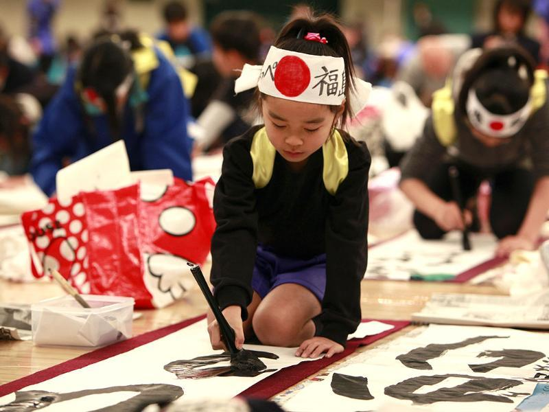 A girl, wearing a headband, uses a large brush for her New Year's calligraphy during a calligraphy contest in Tokyo. (AP Photo/Shizuo Kambayashi)