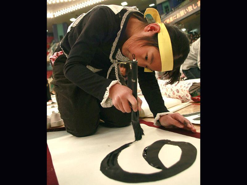 A girl uses a large brush to show her Japanese calligraphy skill on her way to inking 'The sky of the New Year' during the New Year's calligraphy contest in Tokyo. (AP Photo/Shizuo Kambayashi)
