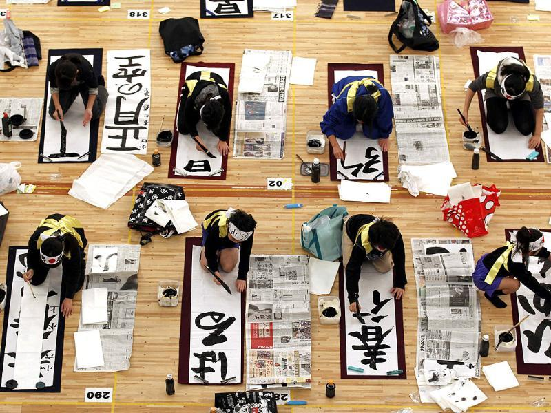 Participants show their Japanese calligraphy skills on their way to inking 'The sky of the New Year,' foreground, and other themes during the New Year's calligraphy contest in Tokyo. (AP Photo/Shizuo Kambayashi)