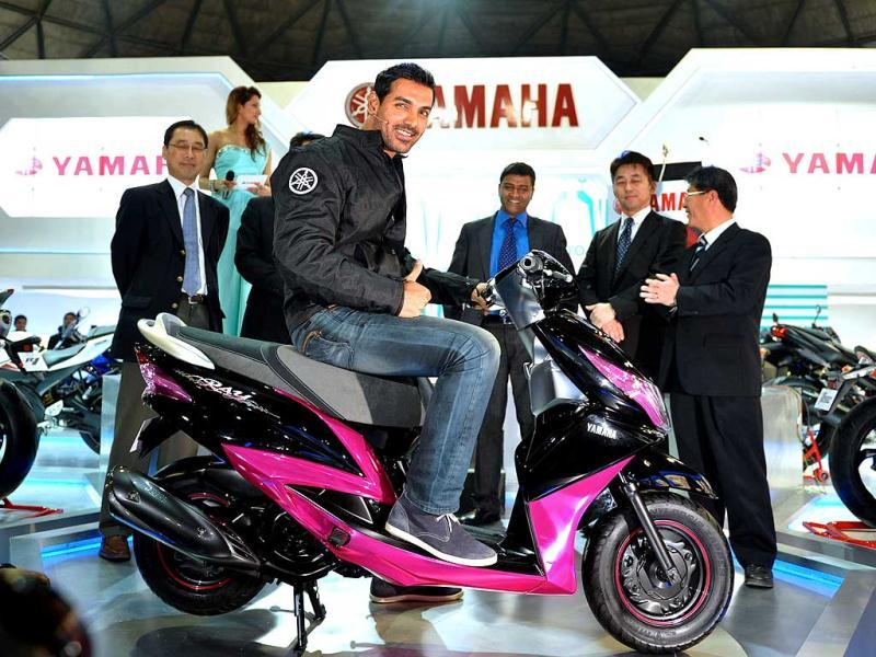 John Abraham sits on a newly launched scooter as he poses with Yamaha representatives during the 2012 Auto Expo in New Delhi. AFP Photo by Sajjad Hussain