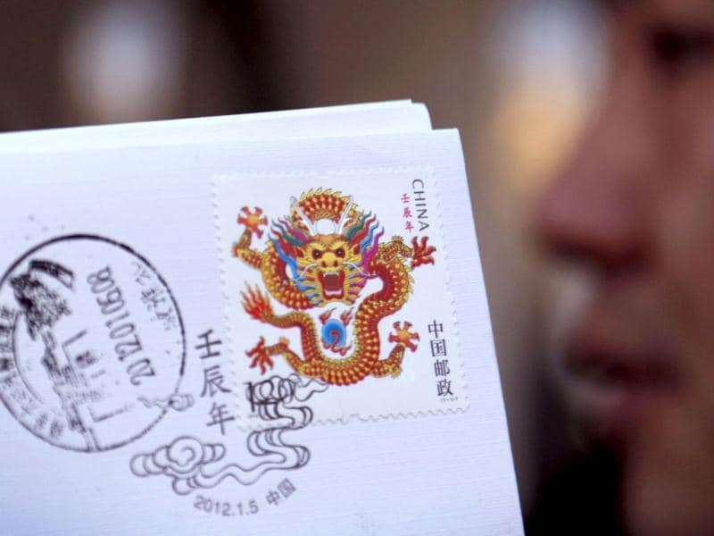 A Chinese worker shows a Year of the Dragon stamp at a post office in Huaibei, east China's Anhui province. A new Chinese postage stamp depicting a dragon, sharp fangs and claws bared, has raised citizen's fears that the post office has put a hard edge on Beijing's efforts to promote China's soft power. AFP Photo