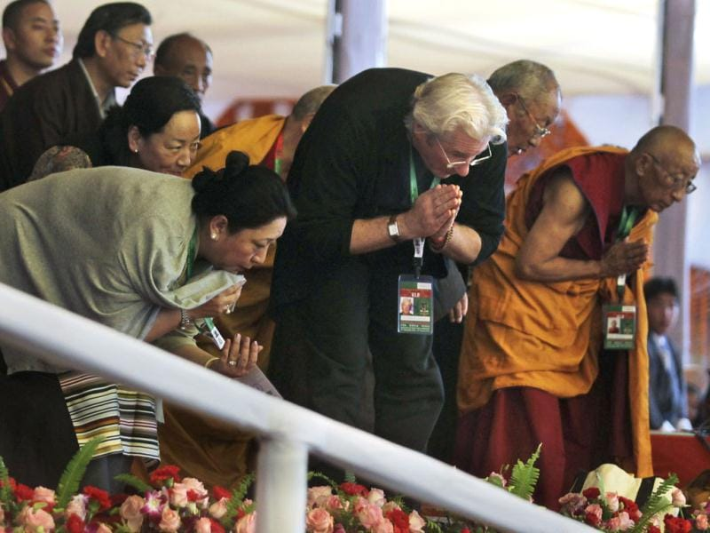Hollywood actor Richard Gere, center, bows in respect as Tibetan spiritual leader the Dalai Lama, unseen, walks past during the Kalachakra Buddhist festival in Bodh Gaya, Bihar, India. (AP Photo/Altaf Qadri)