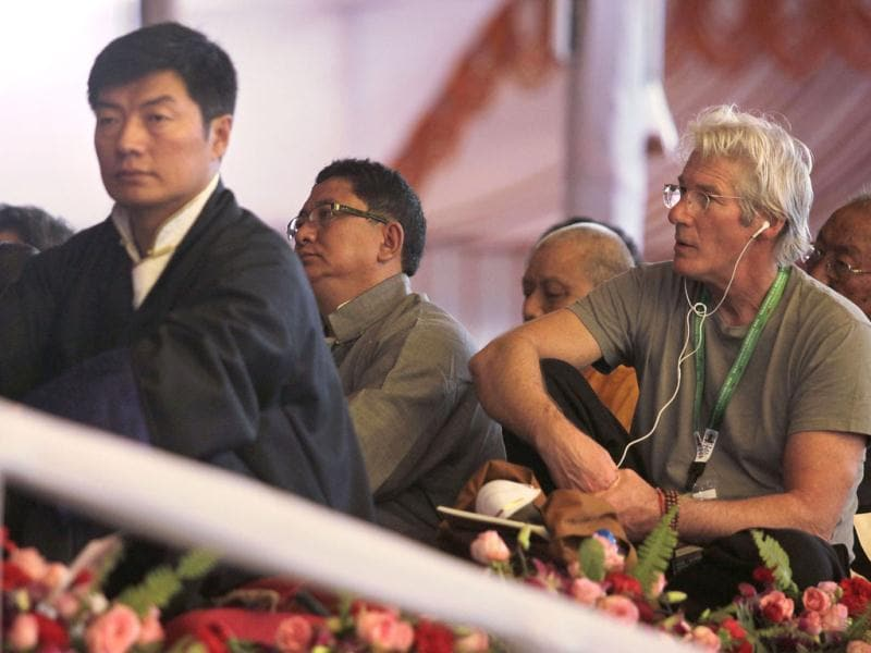 Prime Minister of the Tibetan government-in-exile Lobsang Sangay, left, and Hollywood actor Richard Gere, right, attend a teaching session by Tibetan spiritual leader the Dalai Lama during the Kalachakra Buddhist festival in the town of Bodh Gaya, believed to be the place where Buddha attained enlightenment, in the eastern state of Bihar, India, Thursday. (AP)