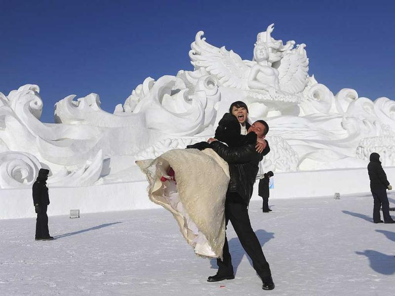 A man lifts his wife in front of a snow sculpture after a group wedding ceremony as part of the 28th Harbin International Ice and Snow festival in Harbin, Heilongjiang province of China. Reuters/Sheng Li