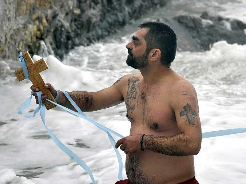 A faithful man retrieves a cross from the sea thrown by a priest for the blessing of the waters during the Epiphany Day at Athens coastal area. AFP photo / Louisa Gouliamaki