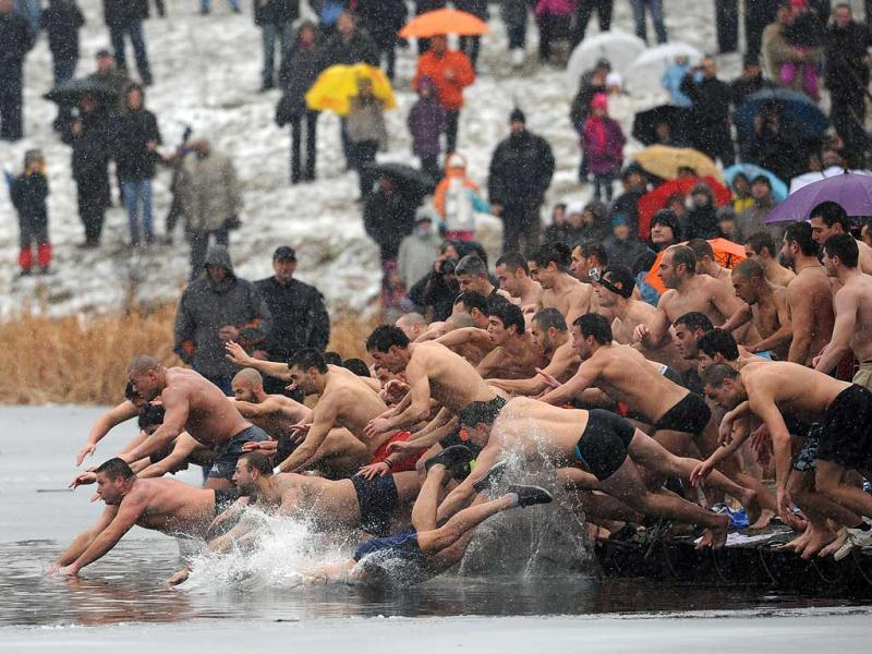 Bulgarians dive into icy water as they compete to catch a cross in the middle of a lake in Sofia as part of Epiphany Day celebrations. It is believed that the man who is the first to grab the cross, thrown into the water by an Eastern Orthodox priest, will be healthy throughout the year. AFP photo / Nikolay Doychinov