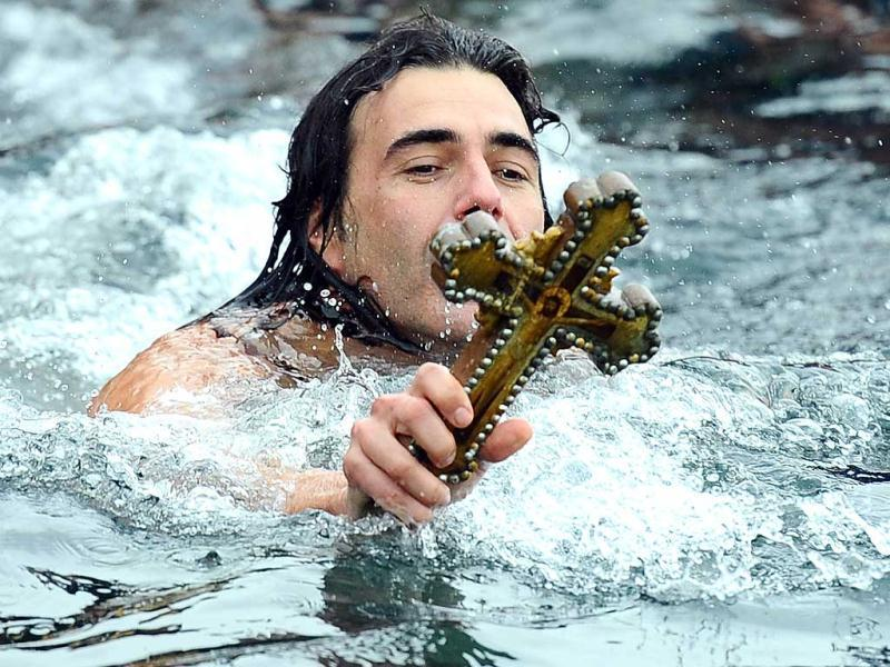 Greek Orthodox swimmer Apostolis Oikomoniv holds the wooden cross in the Bosphorus river's Golden Horn after a mass as part of celebrations of the Epiphany day at the Church of Fener Orthodox Patriarchiate in Istanbul. AFP photo / Mustafa Ozer
