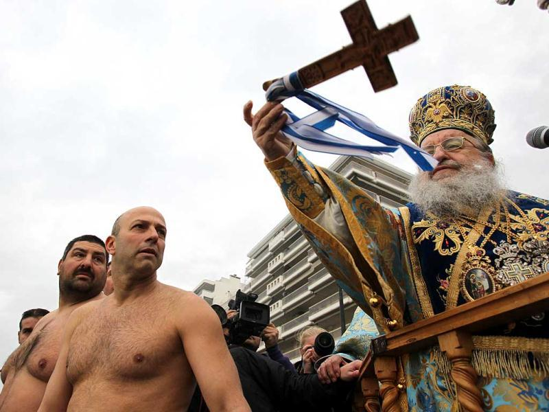 Bishop Anthimos of Thessaliniki throws a wooden cross, to bless the water during an Epiphany ceremony in Greece's northern port city of Thessaloniki. Similar ceremonies to mark Epiphany day were held across Greece on river banks, seafronts and lakes. An Orthodox priest throws a cross into the water and swimmers race to be the first to retrieve it. AP photo / Nikolas Giakoumidis