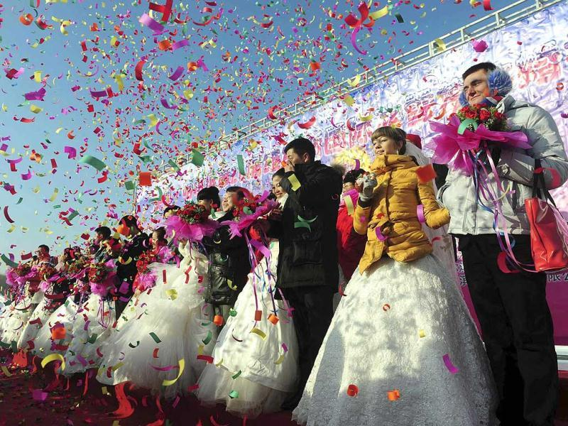 Confetti is thrown at couples during a group wedding ceremony as part of the 28th Harbin International Ice and Snow festival in Harbin, Heilongjiang province of China. Reuters/Sheng Li