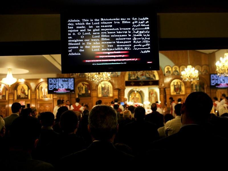A television monitor displays English, Coptic and Arabic languages during Christmas Nativity Liturgy, the start of Christmas, at the Coptic Orthodox Church of St. George in the Brooklyn borough of New York City. Like the Eastern Orthodox Church in Russia, Copts still use the Julian calendar and thus celebrate Christmas on January 7. St. George Church, like other Coptic churches around the country, has witnessed a surge of Christians fleeing Egypt since the start of the Arab Spring. Spencer Platt/Getty Images/AFP