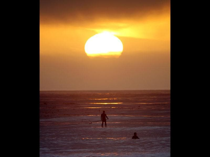 A paddle border and a surfer wait on a new set waves as the sun sets at Swami's beach in Encinitas, Calif. Summer like weather and high surf attracted numerous surfers. AP Photo/Lenny Ignelzi