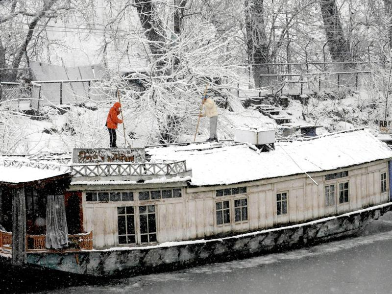 Kashmiri men clear snow off the roof of a house boat in Srinagar. AFP Photo