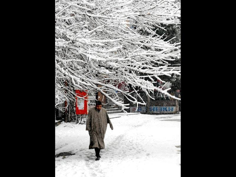 A Kashmiri man walks down a snow-covered street during snowfall in Srinagar. AFP Photo