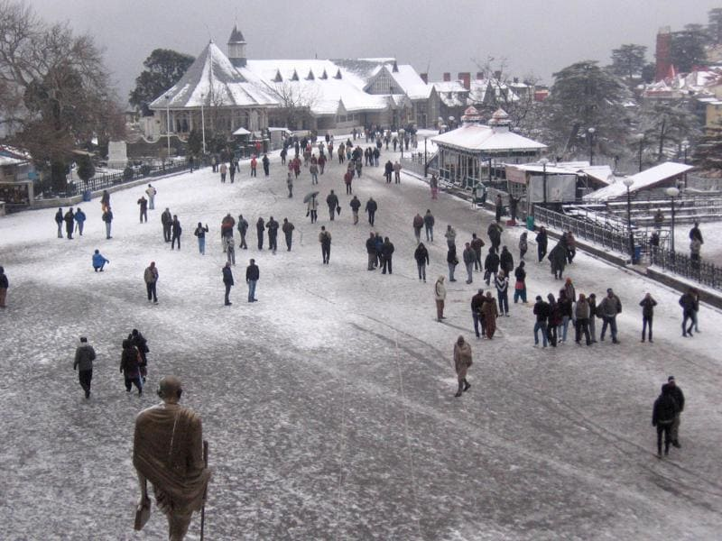 Tourists and local people throng a street to enjoy fresh snowfall in Shimla.