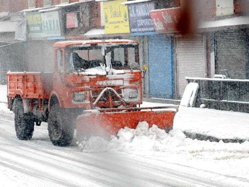 A snow removing machine clears snow off a street during snowfall in Srinagar. AFP Photo
