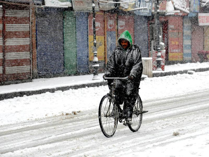 A Kashmiri man rides a bicycle down a snow-covered street during snowfall in Srinagar. AFP Photo