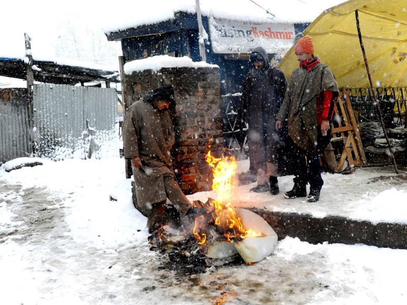 Kashmiri men gather around a fire during snowfall in Srinagar. AFP Photo