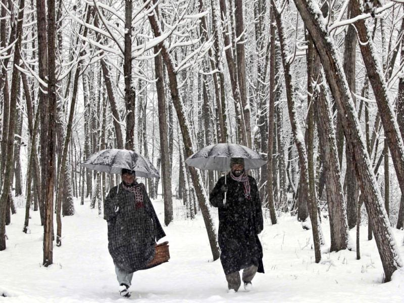Kashmiris holding umbrellas walk on a snow-covered field as fresh snow falls in Srinagar. The Jammu-Srinagar highway has been blocked because of heavy snowfall in the region, according to news reports. AP Photo/Dar Yasin