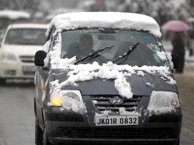 A car covered with snow is driven during a snowfall in Srinagar. Reuters Photo