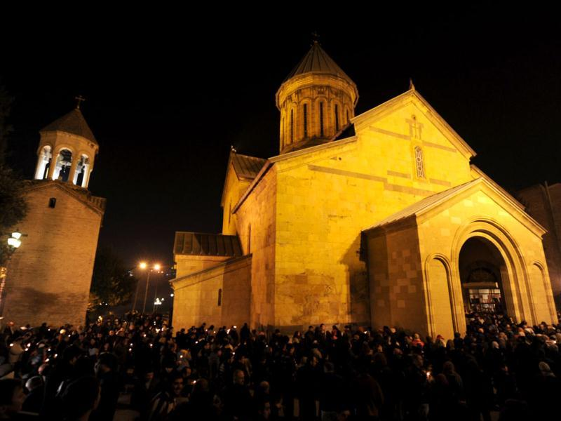 People attend the Orthodox Christmas service near Sioni Cathedral in Tbilisi. (AFP Photo/Vano Shlamov)