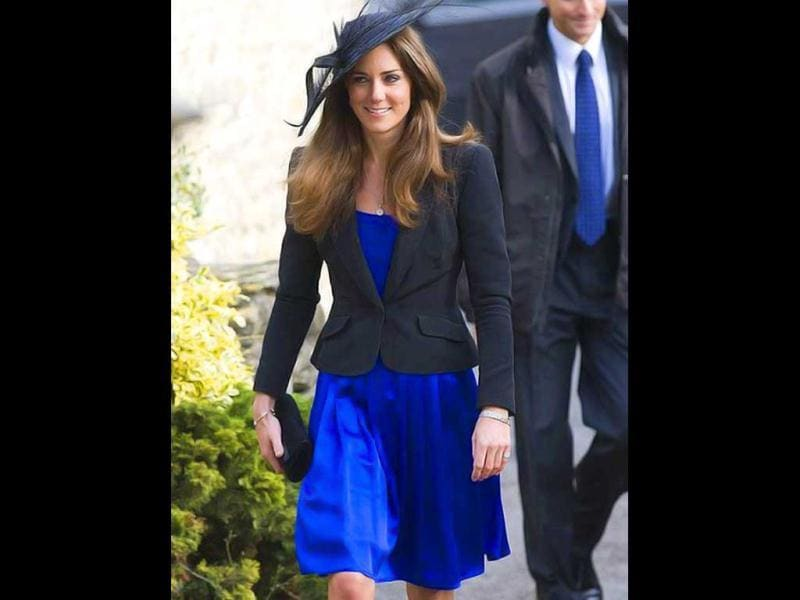 Kate Middleton sizzles in a blue dress with short over coat. Her chic hat surely adds glamour to her attire.