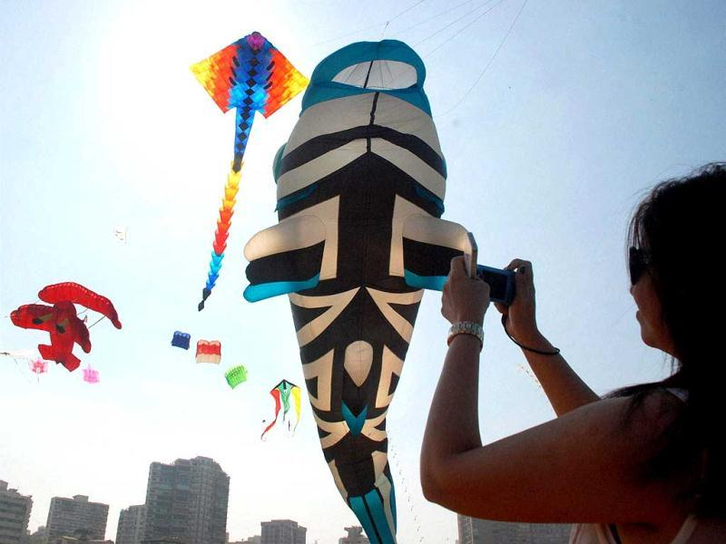 A foreign tourist clicks pictures of various kites during a press preview of the 22nd International Kite Festival (IKF) in Mumbai on Saturday. (PTI Photo)