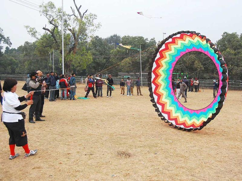 A foreign woman trying to get her saucer-shaped kite airborne at India Gate during the Kite festival 2012 in New Delhi.