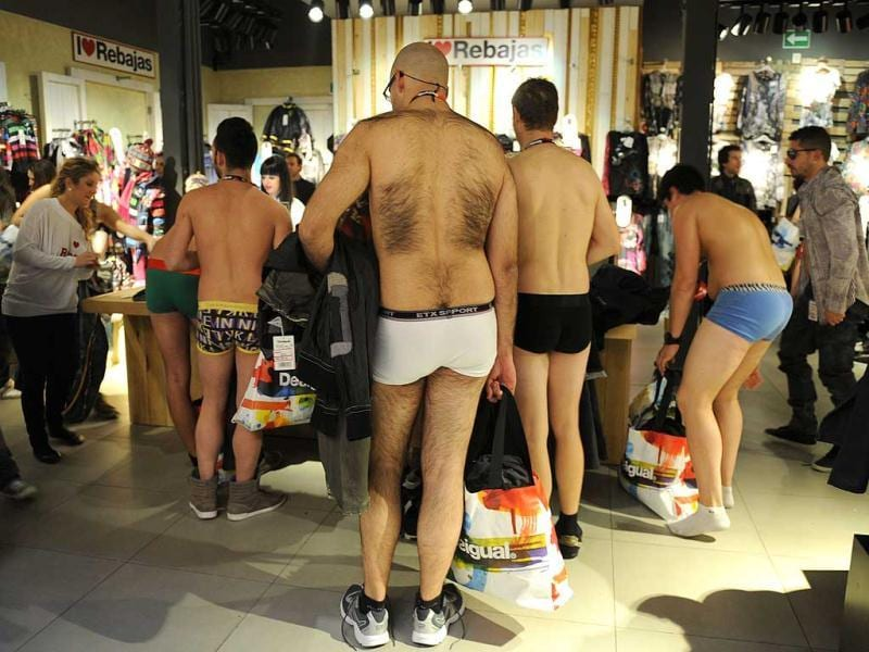 People in their underwear try clothes at a Desigual fashion store during the 'Arrive Half-Naked, Leave Fully Dressed' offer on in Sevilla. AFP photo/ Cristina Quilcer