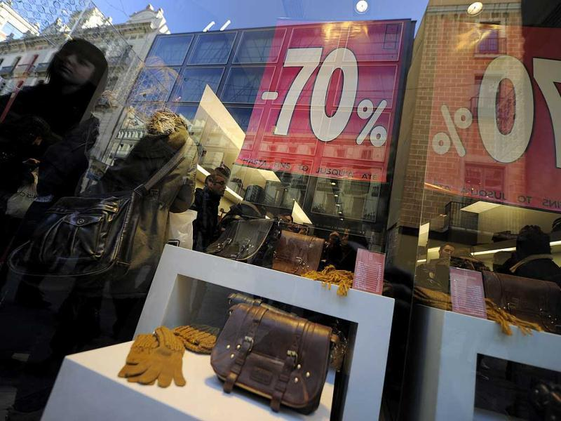 People walks past a window shop announcing sales on the first day of winter sales in Barcelona. AFP photo/ Lluis Gene