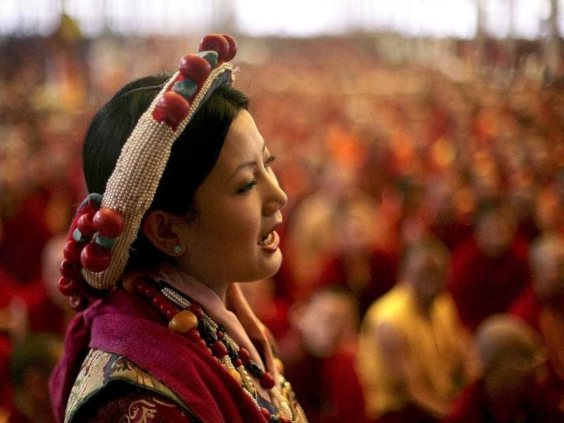 A Tibetan devotee in ceremonial outfit performs in the presence of Tibetan spiritual leader the Dalai Lama, unseen, during the Kalachakra Buddhist festival, in the town of Bodh Gaya, believed to be the place where Buddha attained enlightenment, Bihar. (AP Photo/Altaf Qadri)