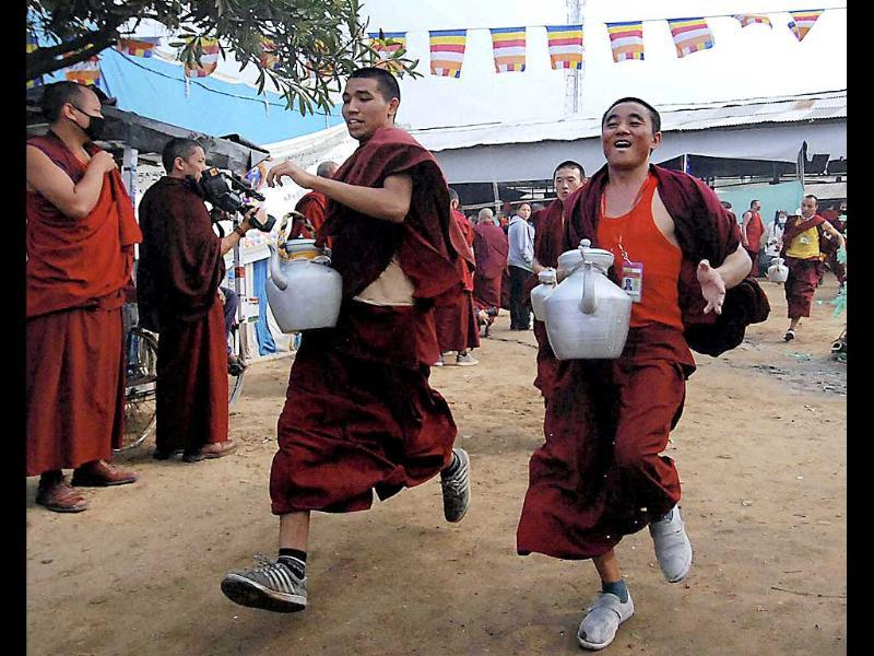 Monks run with kettles to collect tea during the 7th day of the ongoing Buddhist festival Kalachakra in Bodhgaya. PTI Photo