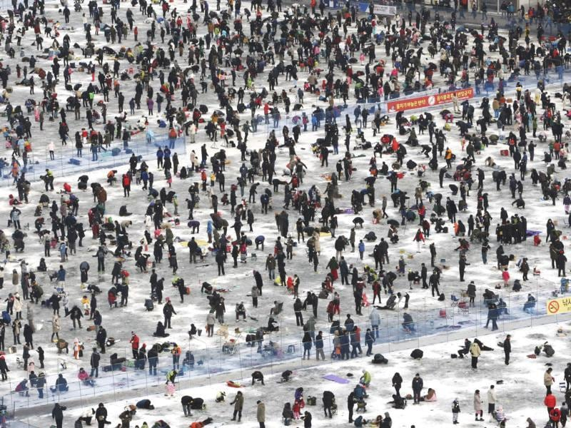 Thousands of anglers cast lines through holes created in the surface of a frozen river during a contest to catch trout in Hwacheon, South Korea. (AP Photo/Ahn Young-joon)