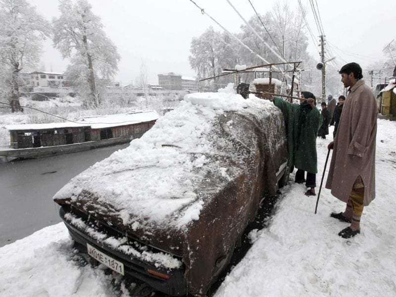 A girl clears snow on her car in Srinagar. (AP Photo/Dar Yasin)