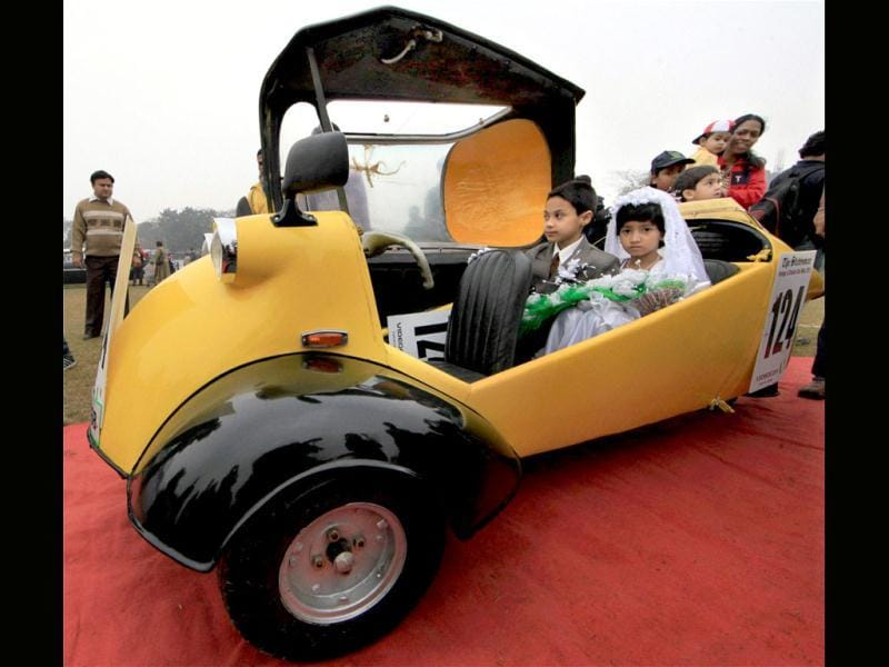 Children dressed like newly married couple sit in their Messersmacmitt car of 1960 during the Vintage car rally in Kolkata. PTI Photo/Swapan Mahapatra