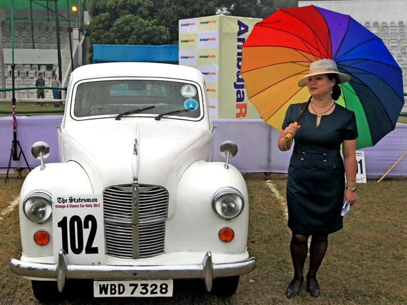 An owner of the Austin 1949 stands besides her car with an umbrella to protect herself from rain during Vintage car rally in Kolkata. PTI Photo/Swapan Mahapatra