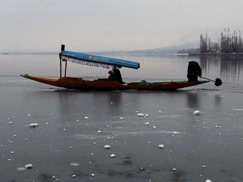 A Shikarawala, or boatman uses the oar to break the frozen part of the Dal lake to create a path for his boat as Kashmir valley reels under freezing weather and received moderate to heavy snowfall across the region over the last two days in Srinagar. PTI Photo by S Irfan