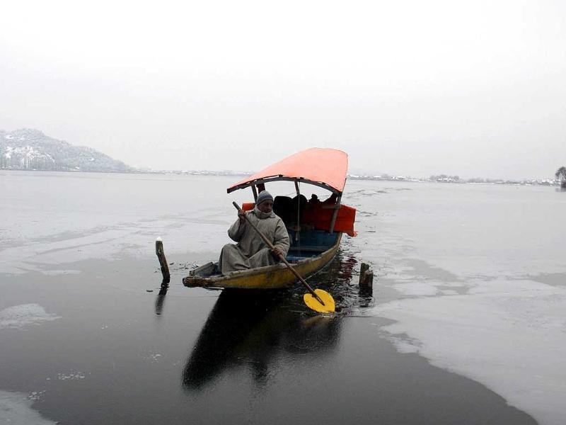 A Kashmiri boatman makes his way through frozen water on the Dal Lake during a cold morning in Srinagar. HT/ WASEEM ANDRABI