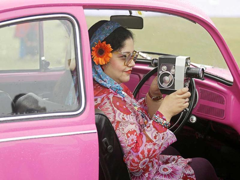 A participant uses a Bolex P4 camera while sitting inside her 1970 Volkswagen 1,285cc classic car in Kolkata. More than 150 vintage cars and two wheelers took part in a vintage and classic car rally. REUTERS/Rupak De Chowdhuri