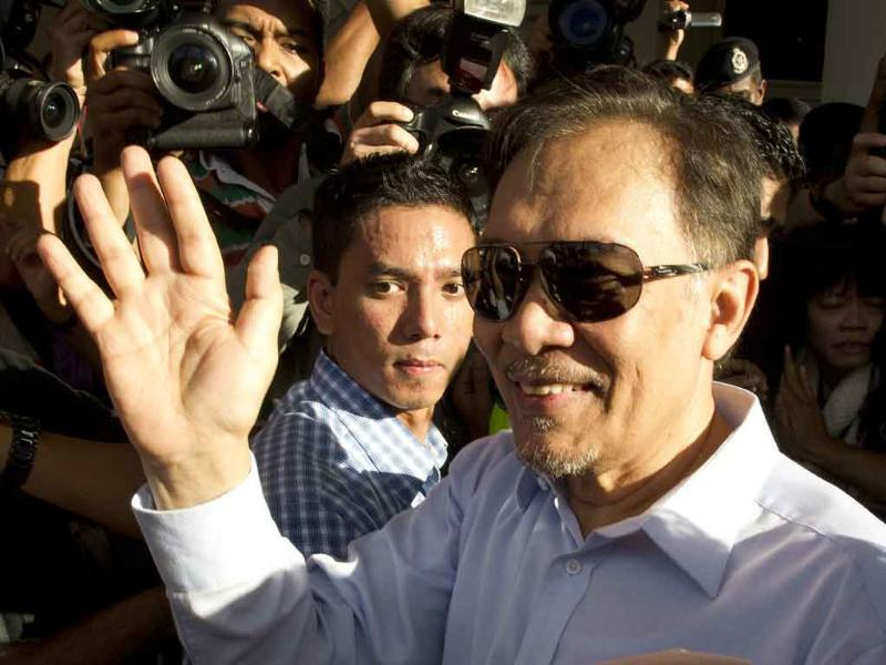 Malaysian opposition leader Anwar Ibrahim waves to his supporters as he enters the court building in Kuala Lumpur. (AFP Photo/Saeed Khan)