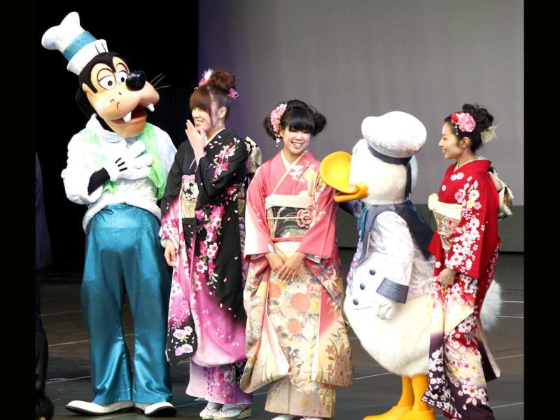 Young Japanese women, who'll be 20 years old this year, have a light moment with Disney characters Goofy, left, and Donald Duck, second right, during a coming-of-age ceremony at Tokyo Disneyland in Urayasu. (AP Photo/Koji Sasahara)